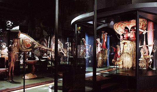 Ein abgedunkelter Raum, darin Vitrinen, in denen Objekte der Ausstellungen Masken der Südsee unter spotlights gezeigt werden