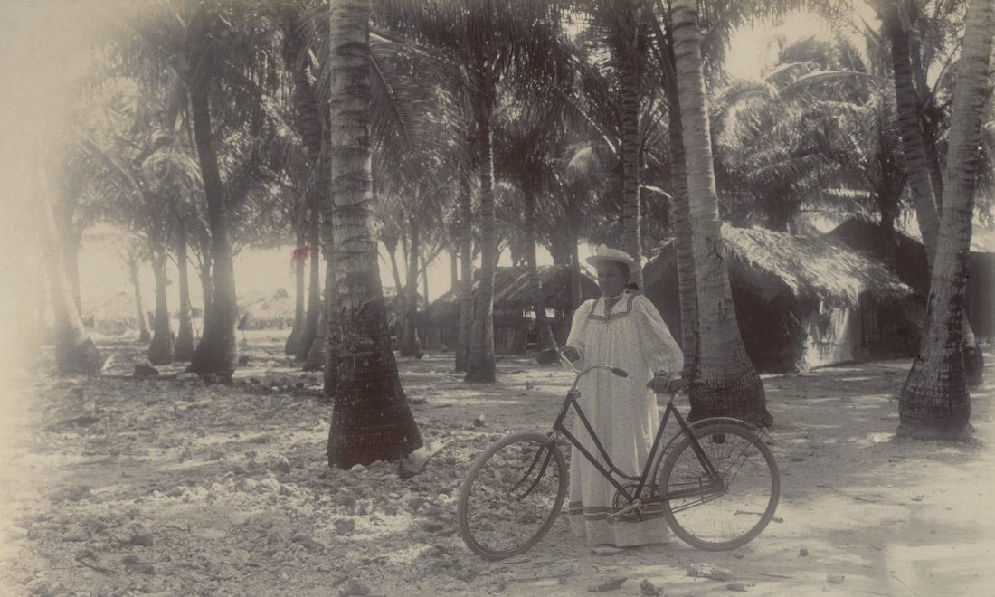 Woman with a bicycle on the beach, photograph