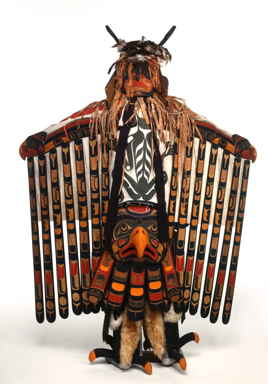 Costume and mask representing a thunderbird, arms spread, colourful