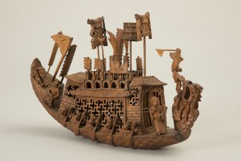 geschnitztes Bootsmodell aus Holz mit Ehrenstandarte, Ruder*innen