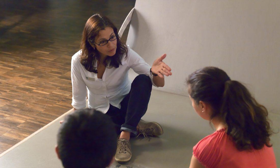 Eine Vermittlerin spricht mit zwei Jugendlichen in einer Ausstellung.