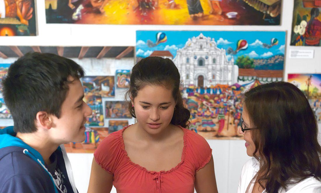 Eine Vermittlerin erklärt Jugendlichen Objekte in einer Museumsvitrine