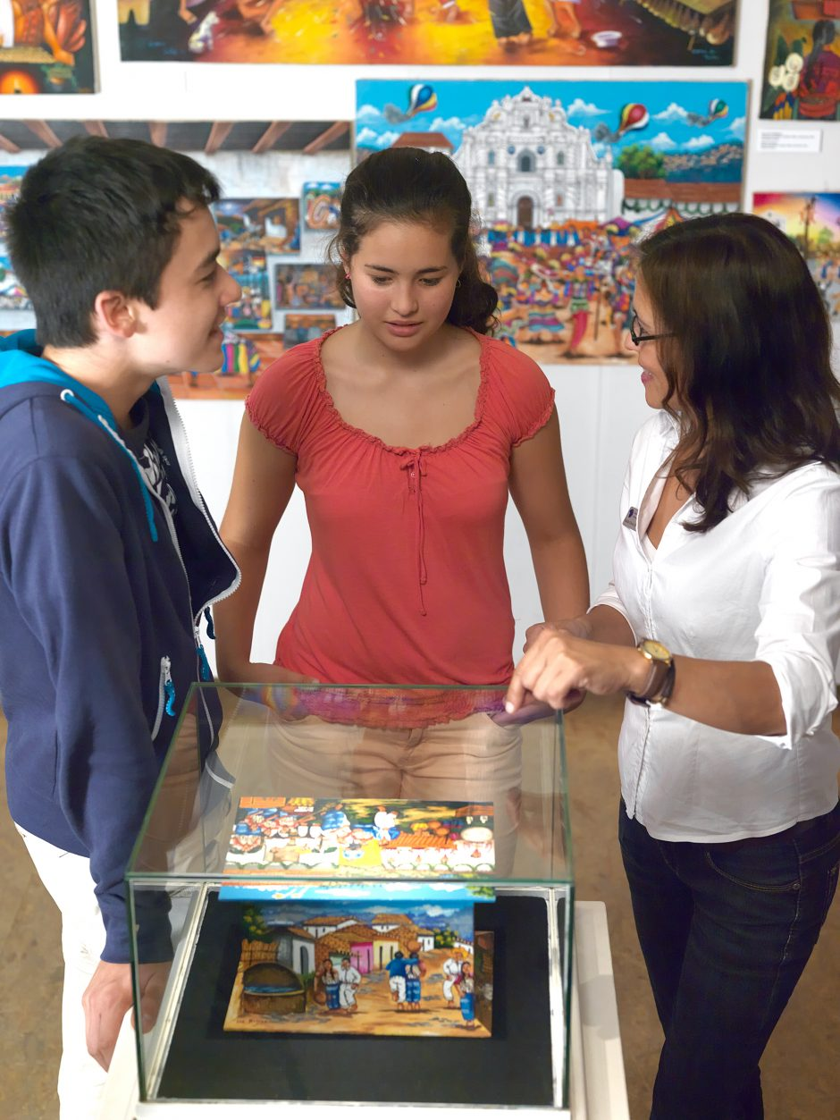 A mediator explains objects in a showcase for adolescents