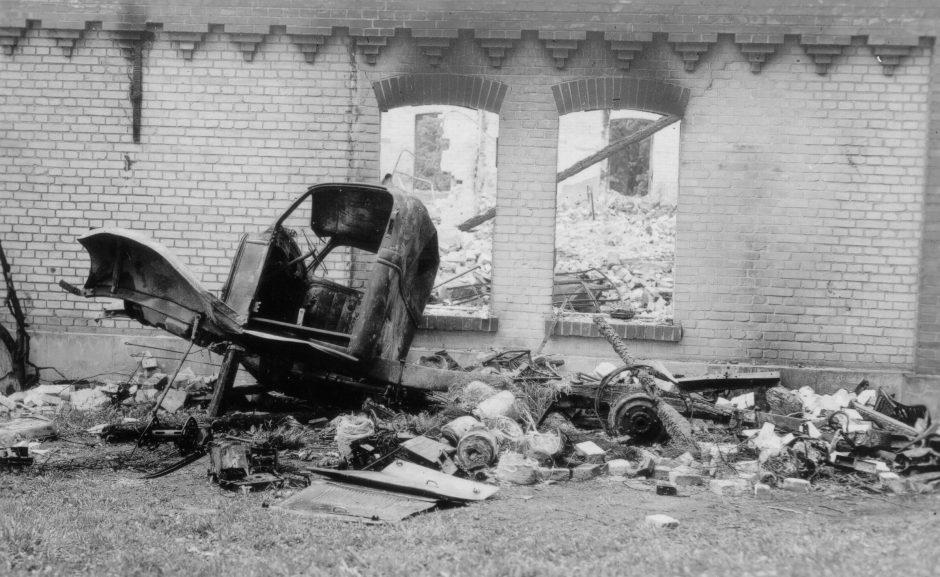 war damage, building, remnants of a vehicle, rubble, b/w photograph