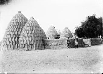 Expedition, expedition participants, Musgum, Musgun, village, architecture, houses, walls, Adolf Friedrich zu Mecklenburg, two men, tropical hat, tropical suit