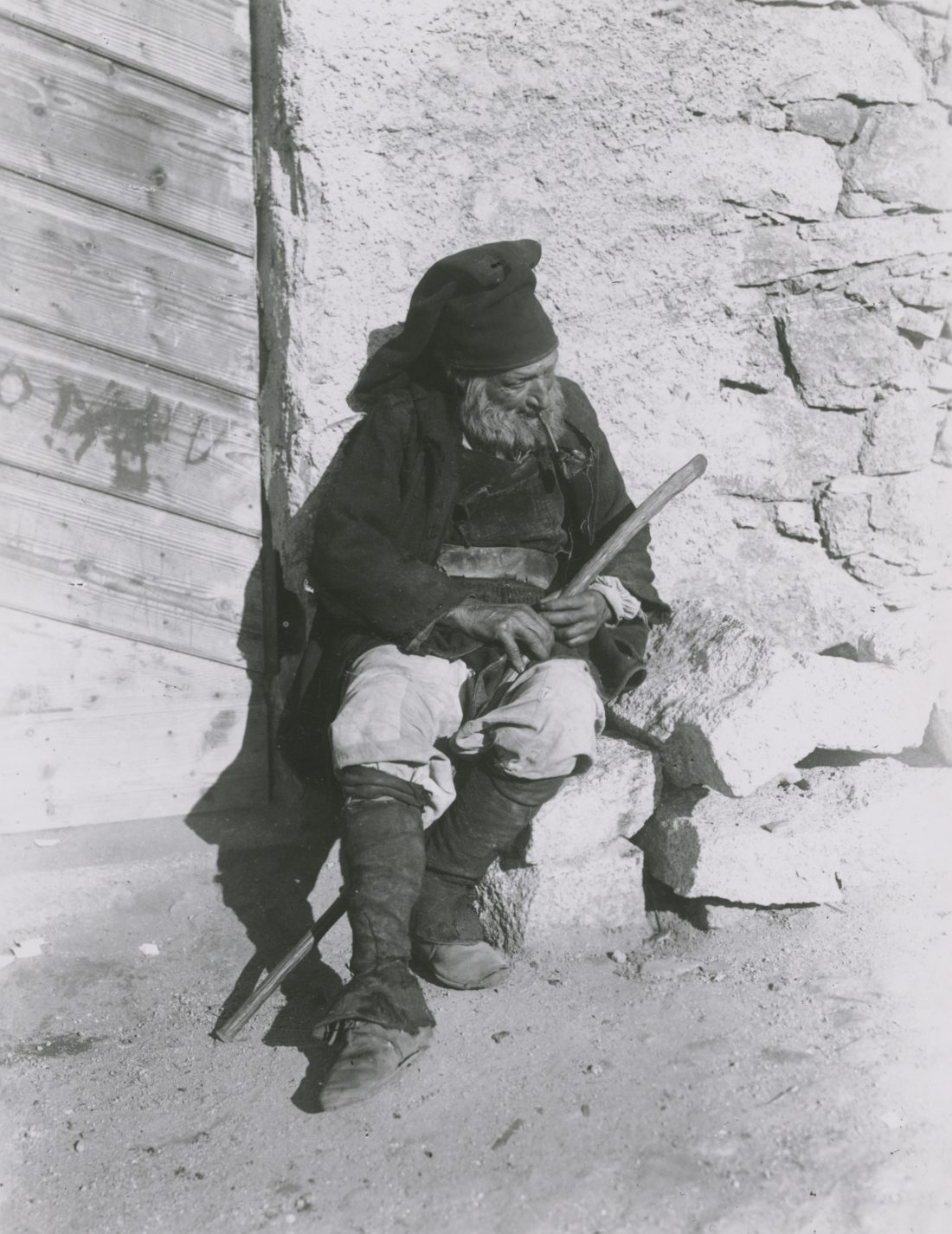 Nuoro, Sardinien, Bauer, alter Mann sitzt auf Mauersteinen, Pfeife, Mütze, Stock, Stab