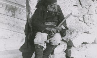 Nuoro, Sardinien, Bauer, alter Mann sitzt an auf Mauersteinen, Pfeife, Mütze, Stock, Stab