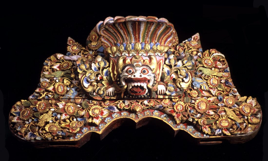 Wooden board with representation of a demon head (boma), embedded in luxuriant floral decoration