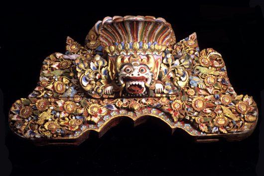 Hölzernes Brett mit Darstellung eines Dämonenkopfes (Boma), eingebettet in üppigen floralen Dekor