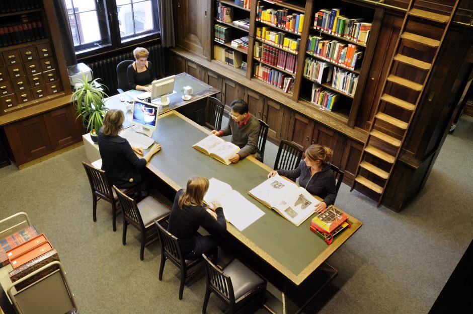 Lesende Personen inklusive beaufsichtigendes Bibliothekspersonal im Lesesaal der Bibliothek