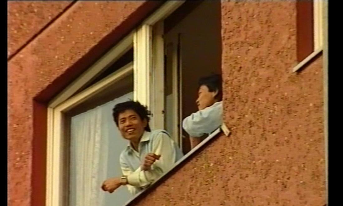 Zwei Personen gucken aus einem Fenster von einem Backsteinbau