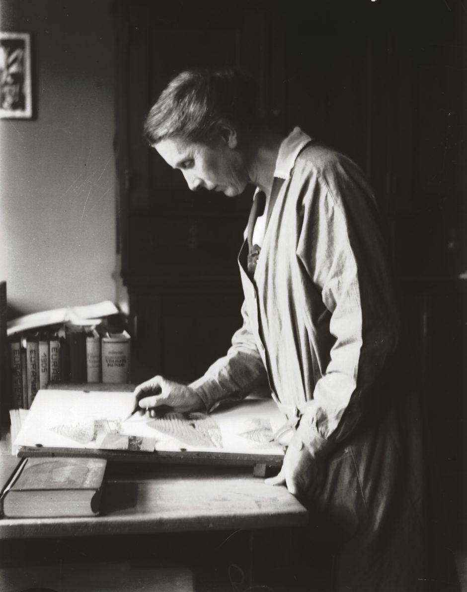Frau beim Zeichnen, Raum, Arbeitstisch, Bücher, s/w Fotografie