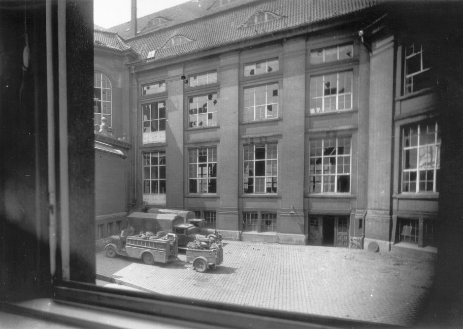 Inner courtyard, destroyed windows, military vehicles, view from a window, b/w photograph