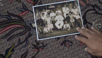 Auf gebatiktem Stoff liegt ein schwarz-weißes Familienfoto, eine Hand berührt es