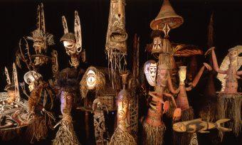Ansammlung von Masken vor dunklem Hintergrund