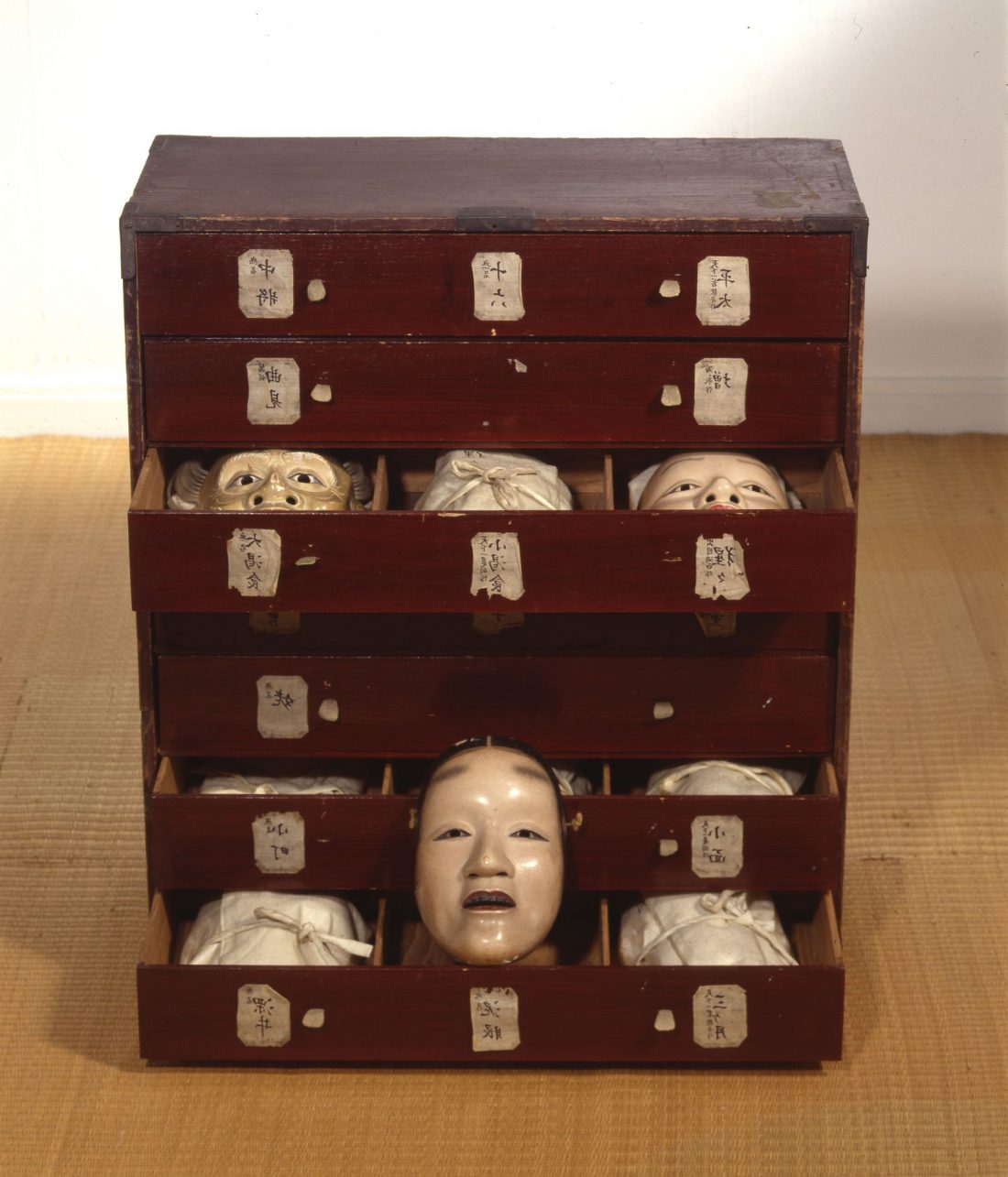 Cabinet with open drawers containing masks