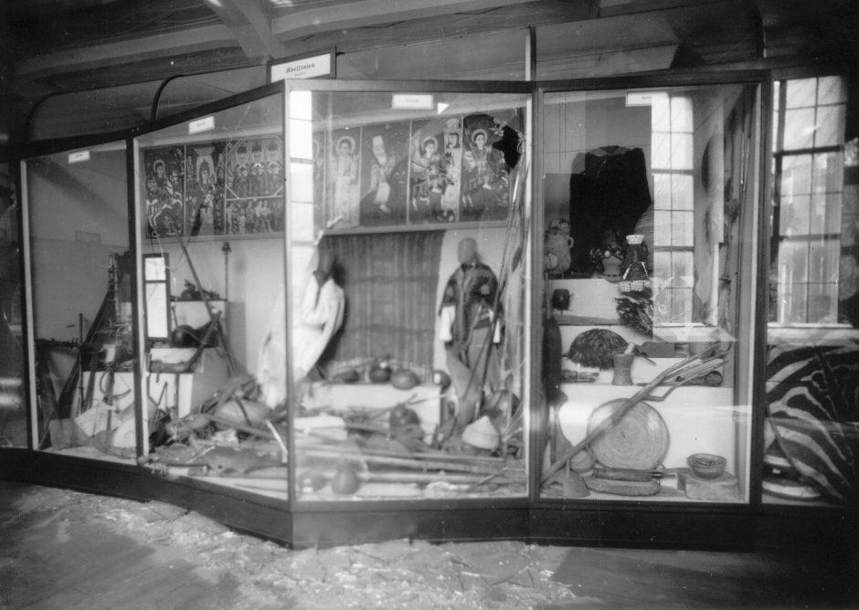 Vitrine, Sammlungsobjekte, Südostasien-Abteilung, Kriegszerstörung, s/w Fotografie