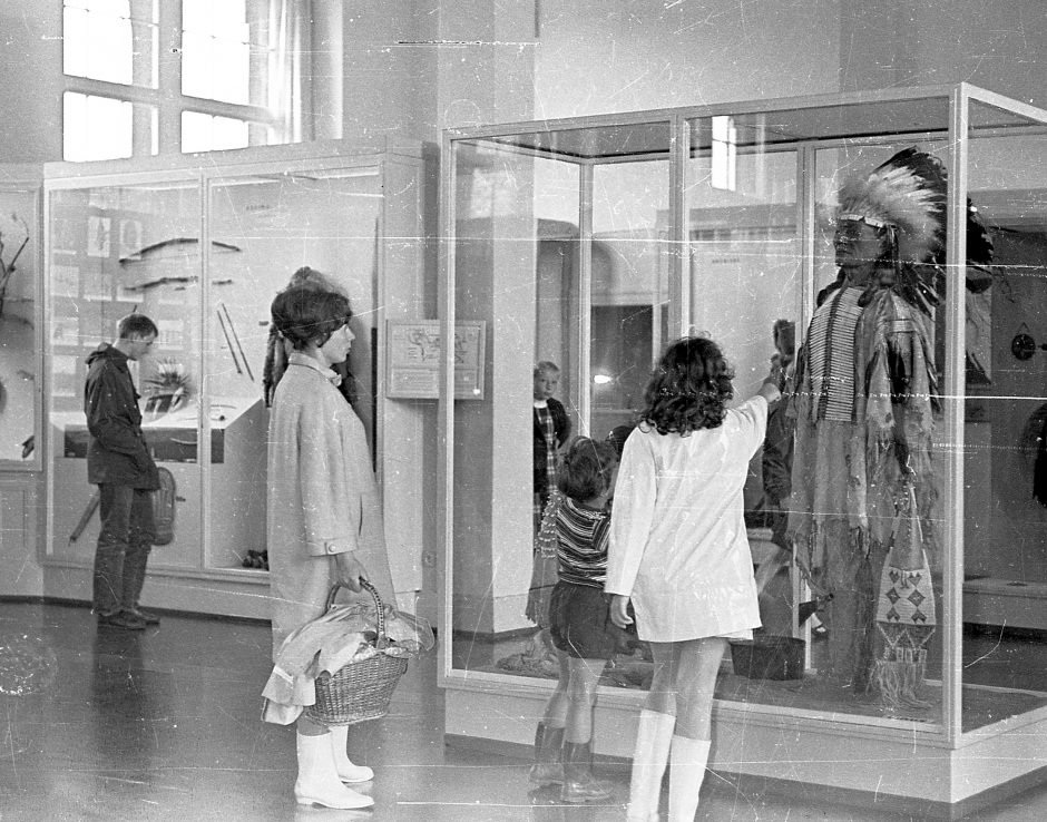 Showcases, dressed mannequin, exhibition visitors, rubber boots, b/w photograph