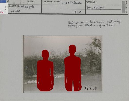 Historische Ikonokarte, künstlerisch bearbeitet, s/w Fotografie, Landschaft, zwei Menschen, rot eingefärbter Schattenriss, Beschriftungen zur Herkunft, künstlerisch bearbeitet von Vitjitua Ndjiharine