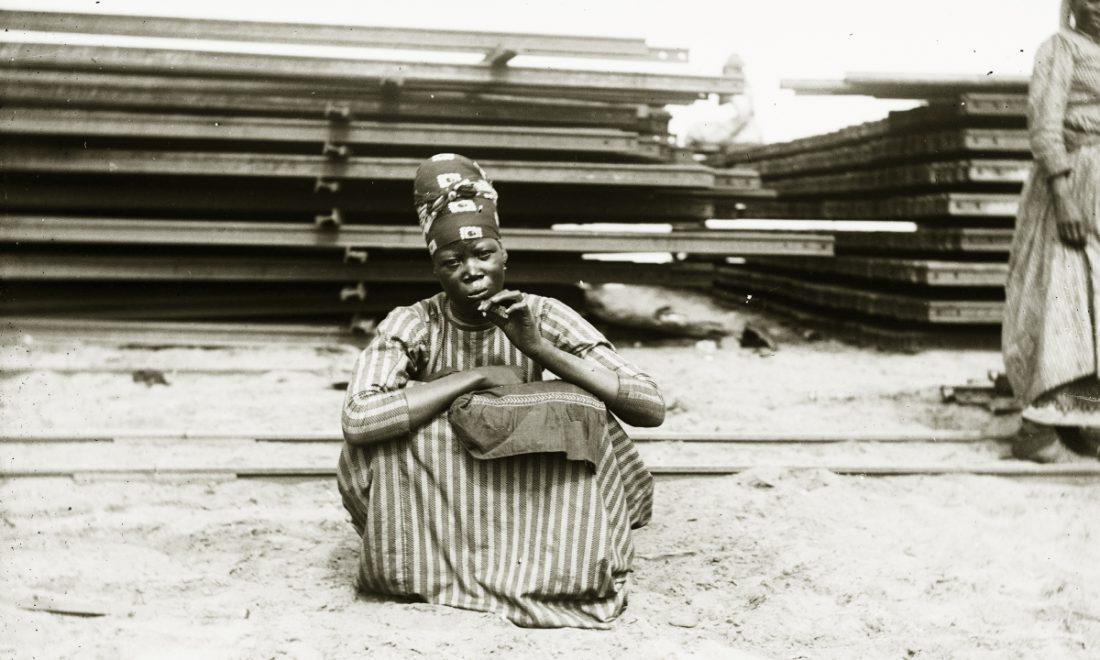 historisches Glasnegativ, Frau vor Zuggleisen sitzend