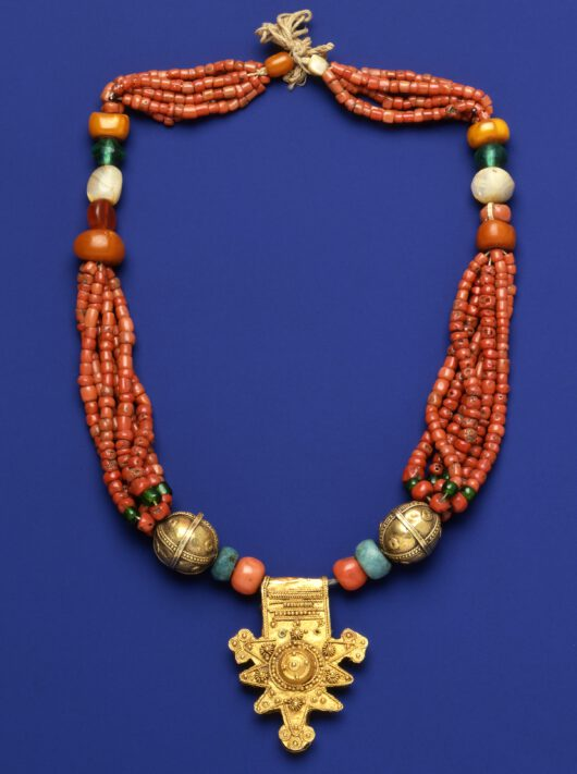 Necklace with mainly red beads and a gold pendant