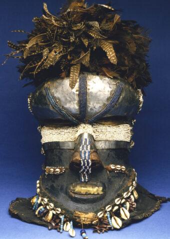 Maske mit Perlen und Muscheln bestickt und Federn obendrauf