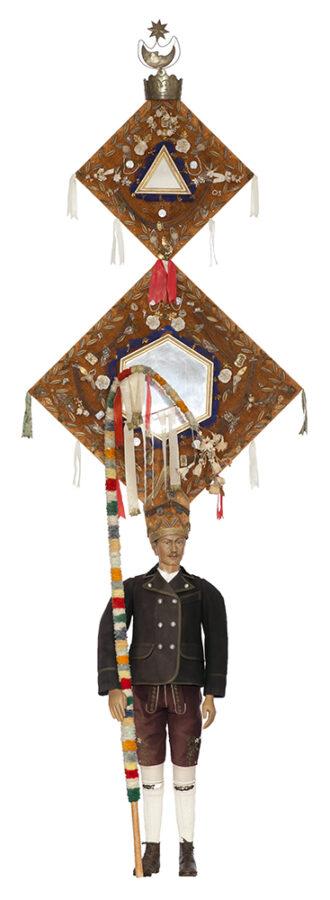 Männliche Figur, die einen Maskenanzug trägt. An der Maske, die sehr hoch ist, sind Spiegel angebracht
