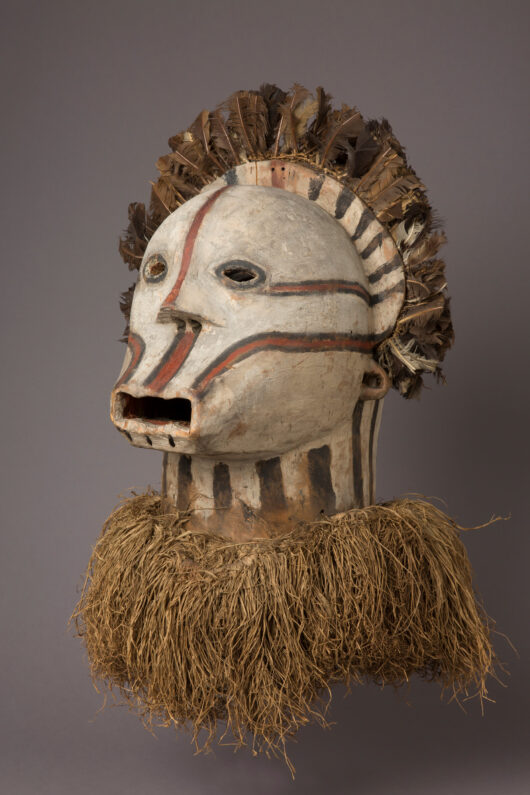 Mask, decorated with bast and feathers, representing a head